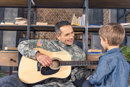 military man playing guitar for son