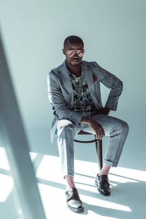 Stylish man in suit posing on chair