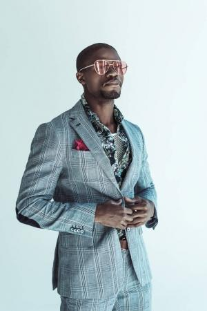 Fashionable man posing in suit and glasses