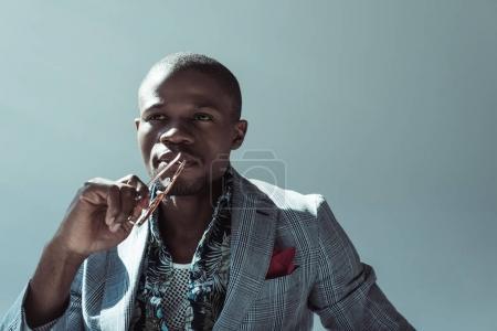 Pensive man holding sunglasses