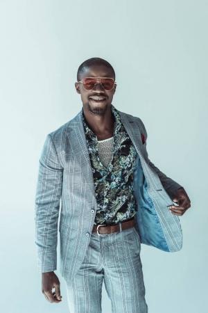 Photo pour Souriant afro-américain dans un costume élégant, en gardant un côté de sa veste et en regardant caméra - image libre de droit