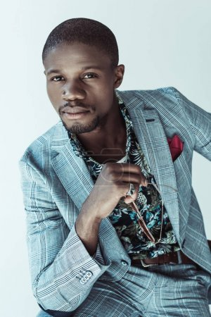 Photo for Stylish african american man in suit holding glasses and looking at camera, isolated on grey - Royalty Free Image