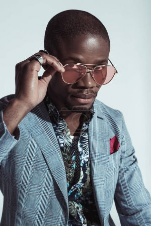 Photo for Fashionable african american man in suit, looking at camera over sunglasses, isolated on grey - Royalty Free Image