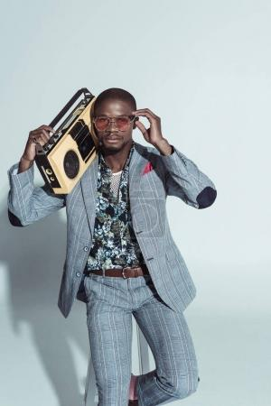 Fashionable man holding boombox