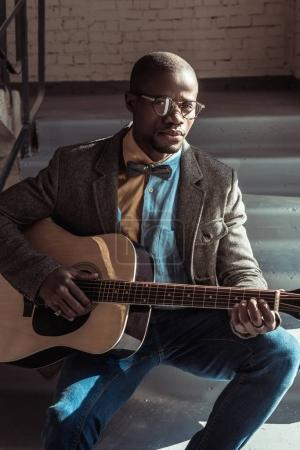 Man sitting on stairs with guitar