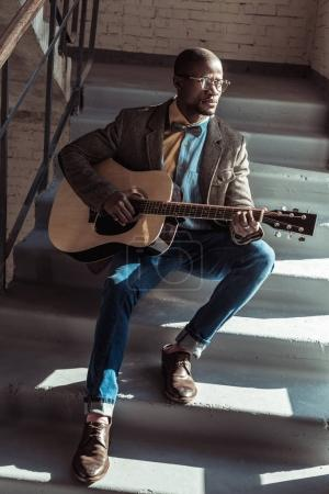 man on stairs playing guitar