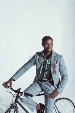Photo pour Bel homme afro-américain en costume élégant, posant sur un vélo en studio - image libre de droit