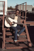 african american man on stairs playing guitar
