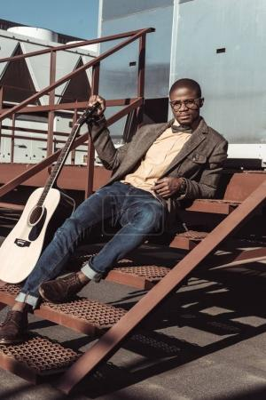 Man posing on stairs with guitar