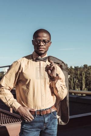 Stylish man holding jacket on shoulder