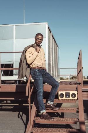 Stylish man posing on stairs