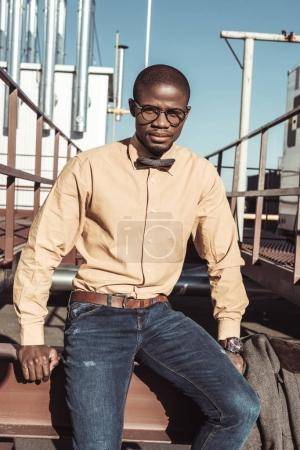 African american man sitting on metal construction