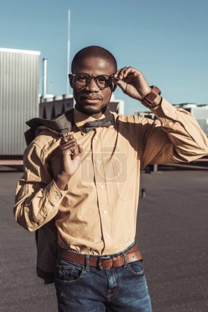 Stylish african american man holding jacket