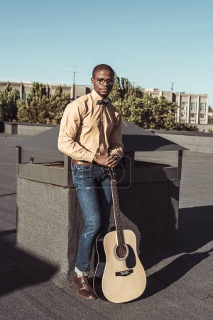 Young african american man holding guitar