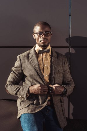 Stylish african american man adjusting jacket