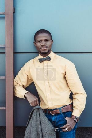Photo pour Bel homme afro-américain en chemise et noeud papillon, posant avec la veste à la main - image libre de droit