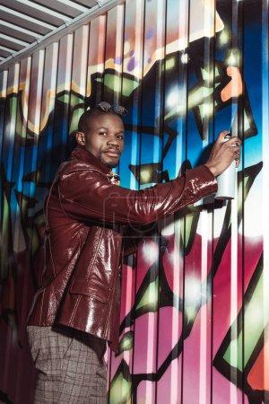 Fashionable man painting graffiti