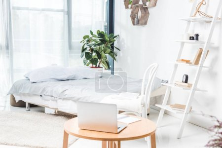 Photo for Laptop on wooden table in cozy bedroom - Royalty Free Image