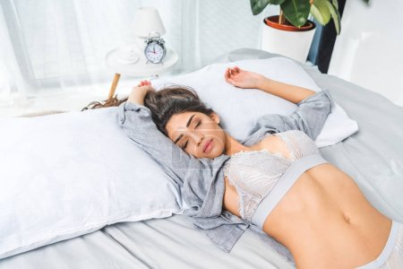 Photo for Beautiful young woman in lace underwear sleeping on bed - Royalty Free Image