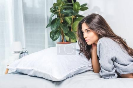 Photo for Beautiful beautiful girl lying on bed and looking away - Royalty Free Image