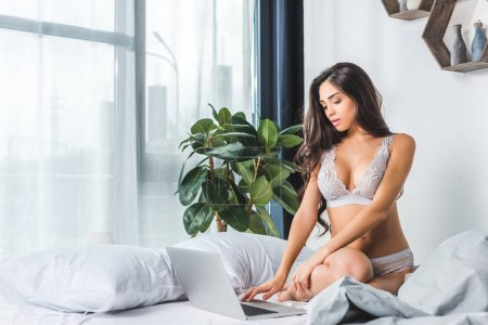 Photo for Seductive young woman in lingerie using laptop on bed - Royalty Free Image