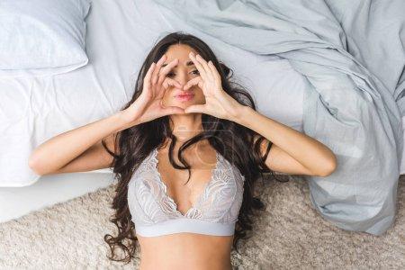 Photo pour Belle jeune femme en lingerie couchée sur le lit et montrant symbole de coeur de main - image libre de droit