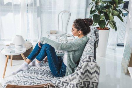Photo pour Vue latérale de fille brune coûteuse assise sur le canapé et regardant loin à la maison - image libre de droit