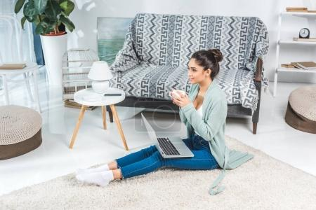 Photo for Attractive brunette girl drinking coffee and using laptop at home - Royalty Free Image