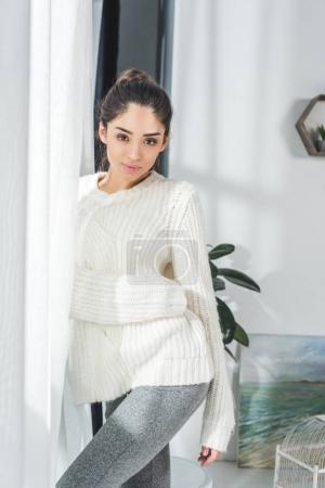 Photo for Beautiful young woman looking at camera while standing at home - Royalty Free Image