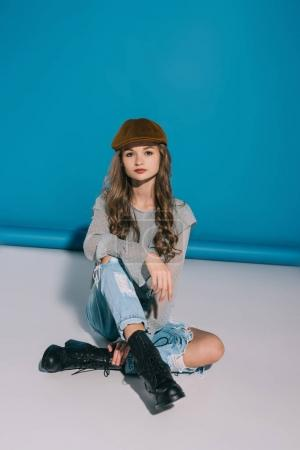 Photo for Attractive teenage girl in trendy outfit looking at camera while sitting in studio - Royalty Free Image