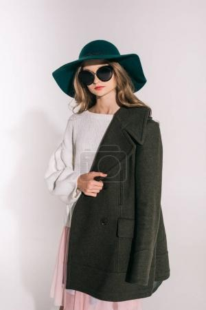 Photo for Beautiful stylish teenage girl in hat, sunglasses and overcoat posing isolated on grey - Royalty Free Image