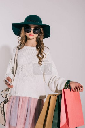 Photo for Stylish teenage girl in black hat and sunglasses holding shopping bags isolated on grey - Royalty Free Image