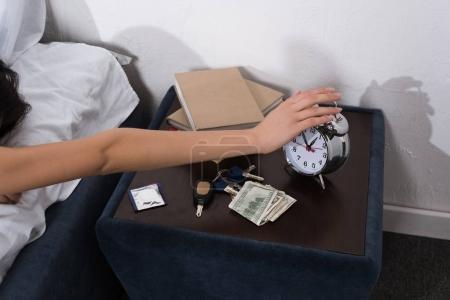 woman setting off alarm clock