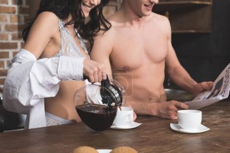 Photo pour Femme verser du café dans des tasses pour le petit déjeuner avec petit ami - image libre de droit
