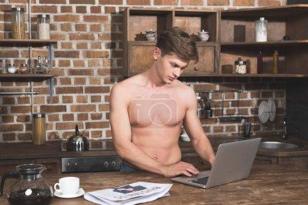 man using laptop at kitchen