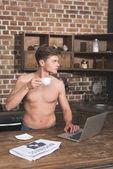shirtless man using laptop