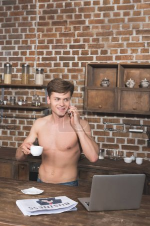 man talking by phone on kitchen