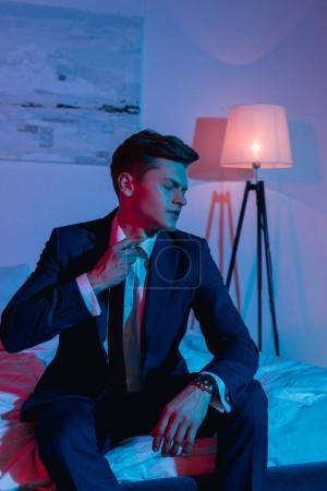 Businessman taking off necktie