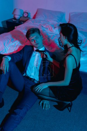 passionate couple sitting on floor in bedroom