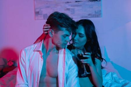 couple sitting on bed with glass of wine