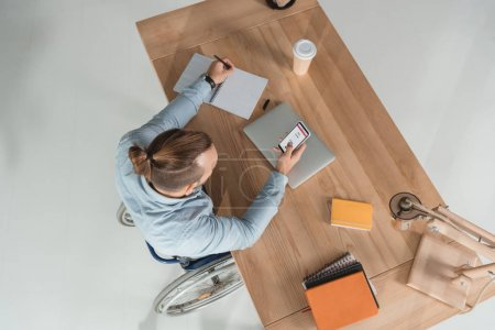 Photo for High angle view of disabled man on wheelchair using smartphone at workplace in office with instagram app - Royalty Free Image