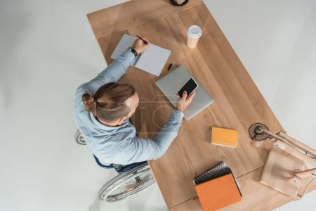 Photo for High angle view of disabled man on wheelchair using smartphone at workplace in office - Royalty Free Image