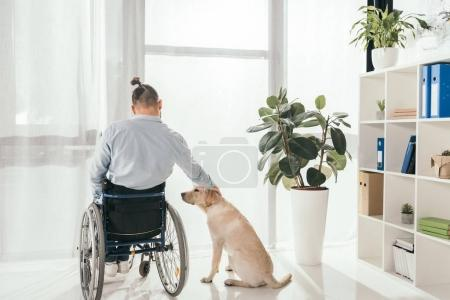 Photo for Disabled man on wheelchair petting his dog in front of window - Royalty Free Image