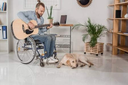 man on wheelchair playing guitar
