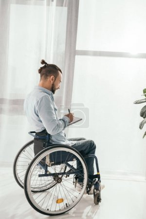 man on wheelchair writing in notebook