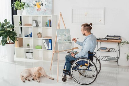 Photo pour Handicapé en fauteuil roulant peignant sur toile tandis que son chien couché sur le sol - image libre de droit