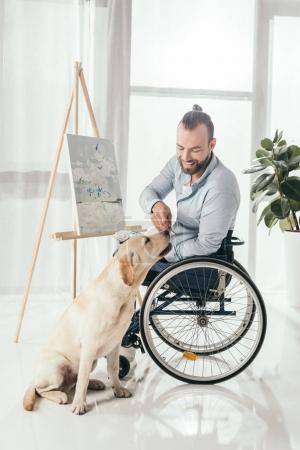 disabled man painting and petting dog
