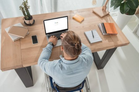 Photo for High angle view of disabled man on wheelchair using laptop with google website - Royalty Free Image