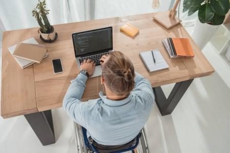 Photo pour Vue grand angle homme handicapé fauteuil roulant codage sur ordinateur portable - image libre de droit