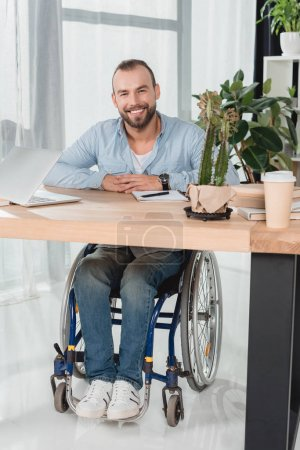 man on wheelchair sitting at office